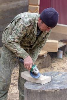 Il carpentiere del falegname del tipo bianco tratta il dettaglio di legno della smerigliatrice