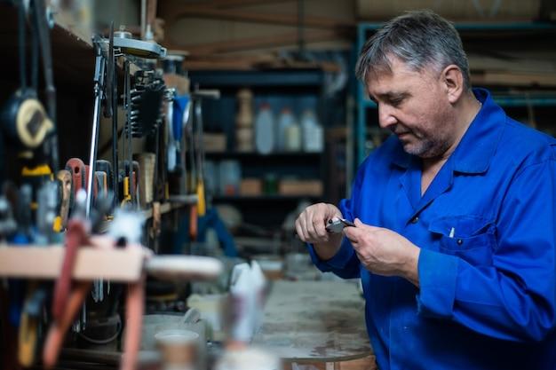 Il carpentiere maturo dell'uomo in tuta sceglie gli strumenti nell'officina