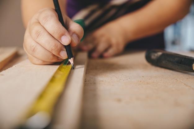 Il carpentiere nell'officina segna sul bordo di legno in officina