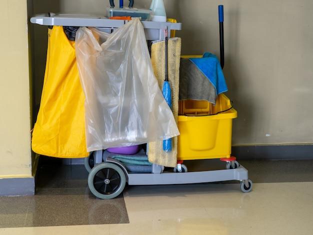 Il carrello degli strumenti di pulizia aspetta per il pulitore. cofano ed insieme di attrezzature per la pulizia nell'ufficio.