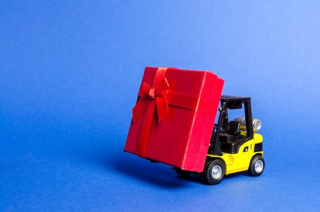 Il carrello elevatore giallo trasporta un contenitore di regalo rosso con un arco.