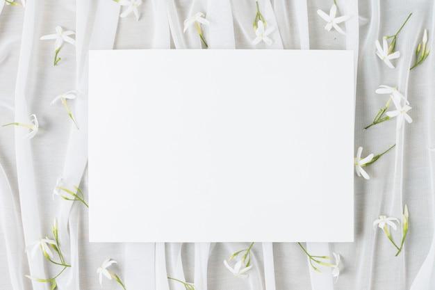 Il cartello bianco di nozze circondato con jasminum auriculatum fiorisce sulla sciarpa