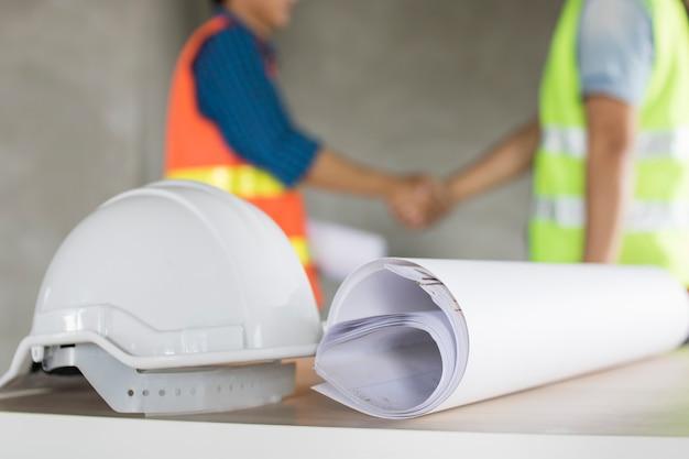 Il casco e la stampa blu sulla tavola con il gruppo dell'ingegnere agitano il fondo delle mani