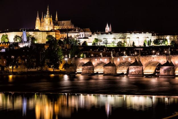 Il castello di praga e il ponte carlo sul fiume moldava di notte a praga, repubblica ceca