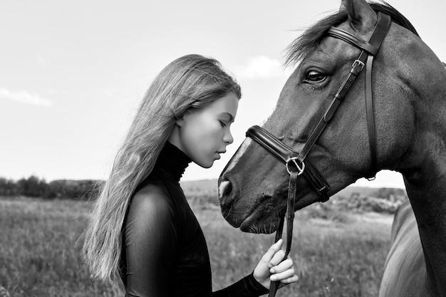 Il cavaliere della ragazza sta accanto al cavallo nel campo. ritratto di moda