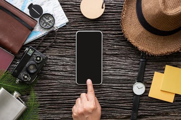 Il cellulare di tocco della mano di vista superiore sulla roba dell'esploratore viaggia con l'oggetto sul vecchio scrittorio di legno.