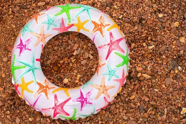 Il cerchio gonfiabile variopinto del bambino si trova sulla riva.