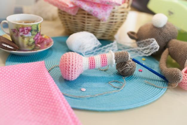 Il cestino da cucito a maglia e una tazza di caffè sul tavolo.