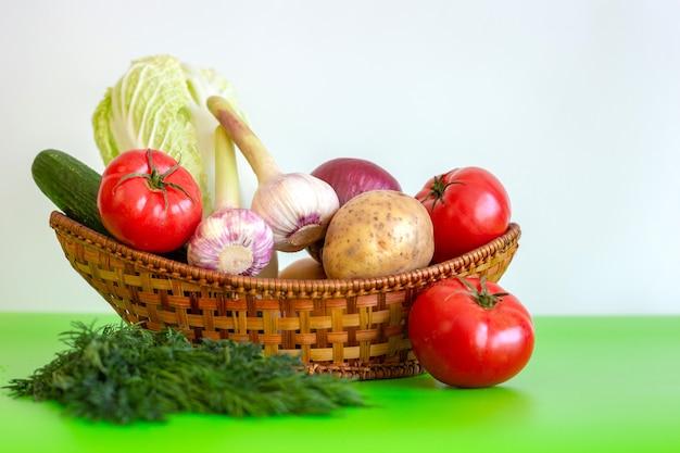 Il cestino di vimini è sul tavolo con vegetariano salute alimenti sul tavolo verde