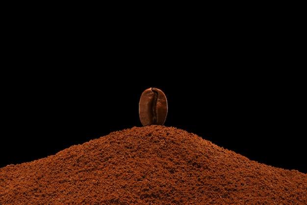 Il chicco di caffè di recente arrostito sta su una dispersione di caffè macinato su un fondo nero