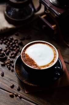 Il chicco di latte e di caffè della tazza di caffè con il gocciolatore del caffè ha messo sulla tavola di legno.