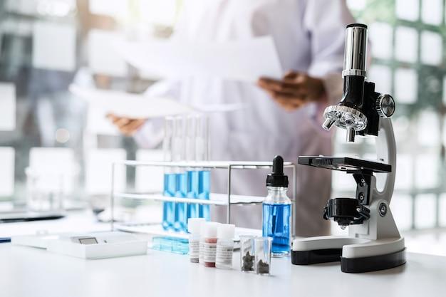 Il chimico sta analizzando il campione in laboratorio con il microscopio