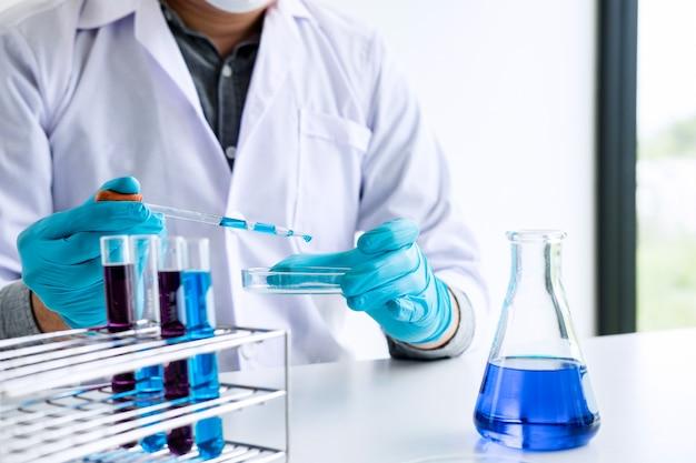 Il chimico sta analizzando il campione in laboratorio con le attrezzature e gli esperimenti scientifici