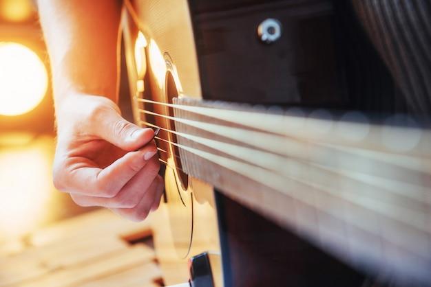 Il chitarrista suona la chitarra su fondo di legno