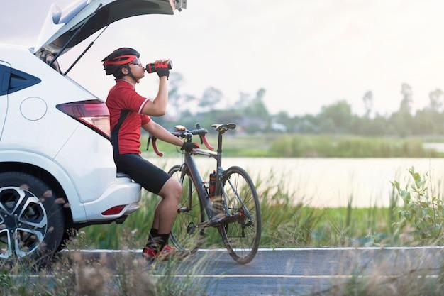 Il ciclista beve l'acqua dopo la corsa in bicicletta