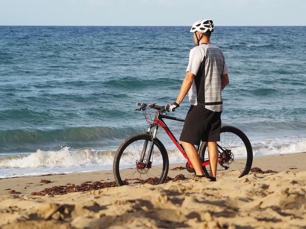 Il ciclista che riposa sulla spiaggia dell'oceano atlantico guarda verso l'oceano. vista posteriore. tramonto serale.