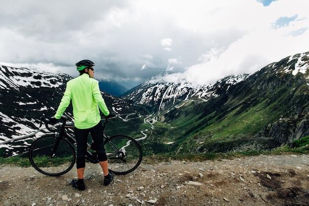 Il ciclista che sta con le bici della strada su fondo di belle montagne alpine abbellisce