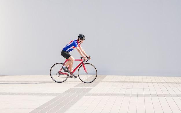 Il ciclista dell'atleta guida su una bici su una parete della luce bianca