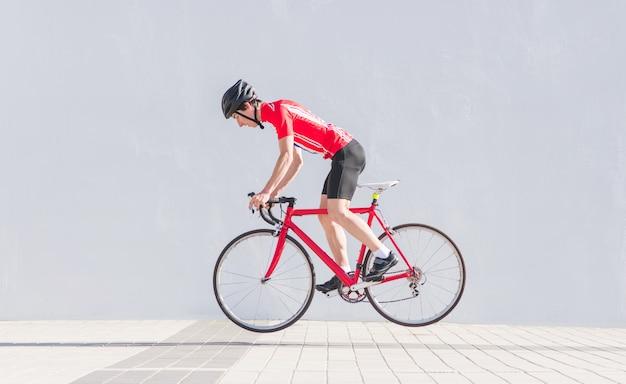 Il ciclista in un casco e vestiti in bicicletta salta su una bici da strada rossa su un muro bianco
