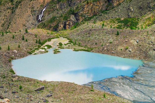 Il cielo blu ha riflesso sul bello lago vicino al pendio di pietra della montagna. cascata sul fianco della montagna. superficie dell'acqua azzurra. sabbia bianca e grandi pietre sulla riva. paesaggio insolito della natura di altai.