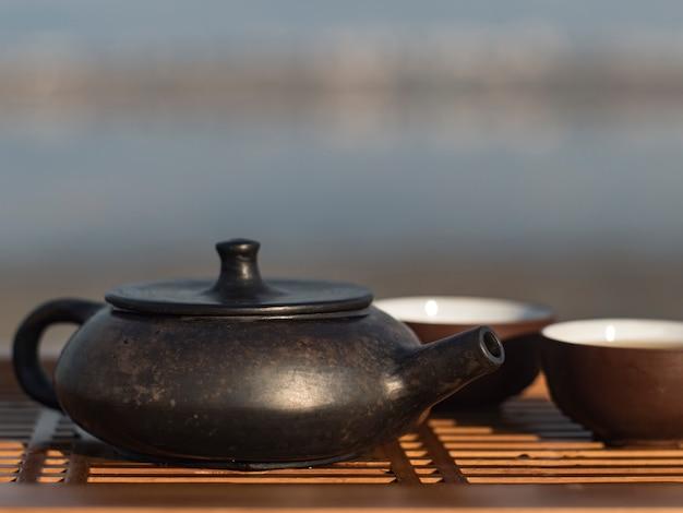 Il cinese d'annata ha messo con la teiera yixing di cerimonia di tè nero su fondo verde