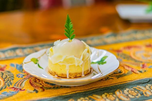 Il cioccolato bianco assortito con la torta della bacca è servito in un piatto bianco