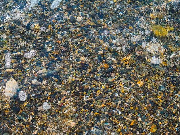 Il ciottolo arrotondato a mare risplende attraverso l'acqua limpida