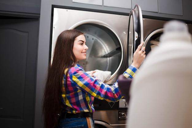 Il client della lavanderia automatica self service estrae le cose dall'asciugatrice