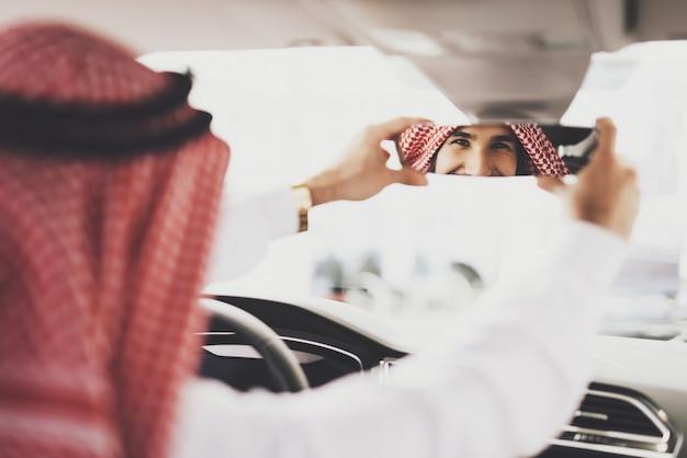 Il cliente arabo acquista gli occhi dell'auto nello specchietto retrovisore