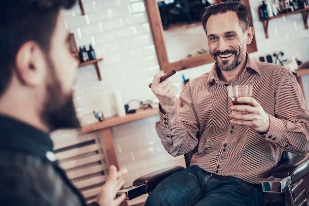 Il cliente beve whisky in un negozio di barbiere