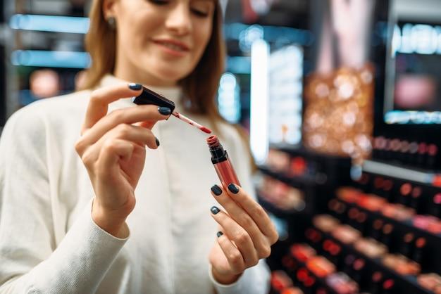 Il cliente femminile osserva il rivestimento del labbro nel negozio di cosmetici.