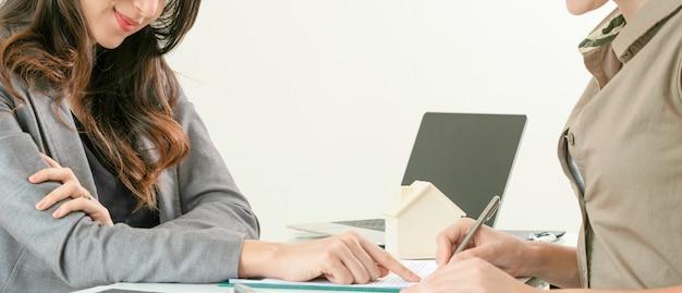 Il cliente firma il documento per comprare la casa e il bene immobile