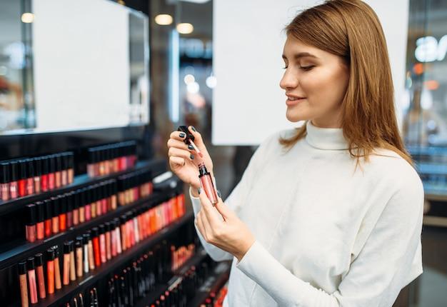 Il cliente guarda la matita per le labbra nel negozio di cosmetici