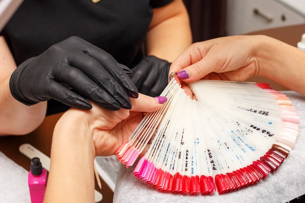 Il cliente nel salone della manicure sceglie il colore dello smalto per unghie.