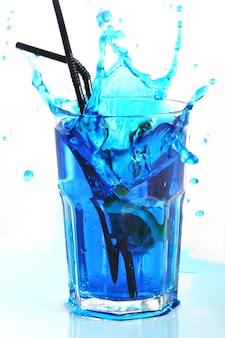 Il cocktail blu con spruzza isolato su bianco
