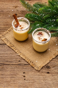 Il cocktail dello zabaione in due vetri ha sistemato con la decorazione di natale sulla vecchia tavola di legno. ramo di albero sempreverde, neve artificiale, tovagliolo di tela di sacco