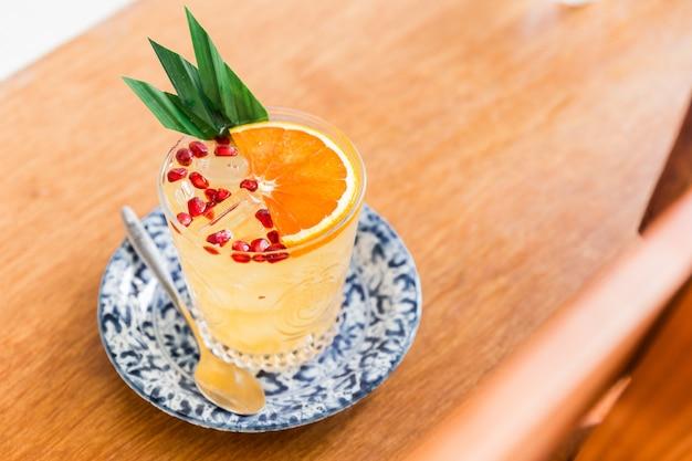 Il cocktail fruttato all'arancia che si mescola con polpa d'arancia e melograno a fette in un bicchiere. decorato con foglie di banano.