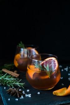 Il cocktail negroni su nero è servito con una fetta di arancia e rosmarino.