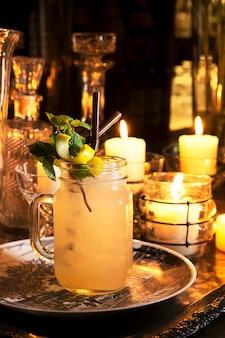 Il cocktail serve sulla tavola con il fondo della decorazione della candela