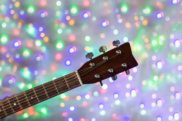 Il collo della chitarra acustica sul fondo del bokeh della luce di natale