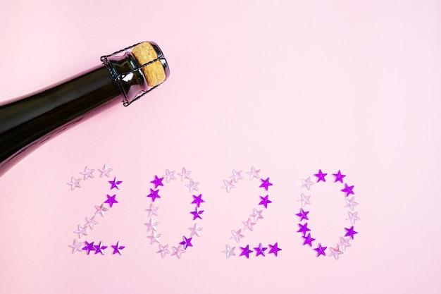 Il collo di una bottiglia di champagne e un bicchiere su una superficie rosa pastello. nelle vicinanze si trovano strass rosa e viola a forma di stelle e compongono il numero 2020.