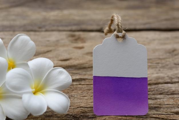 Il colore dell'acqua dipinto sull'etichetta dell'etichetta decora con i fiori di plumeria sulla tavola di legno