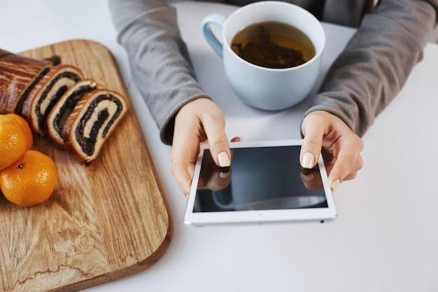 Il colpo del primo piano della donna passa la tenuta della compressa digitale. la ragazza ama i weekend in un'atmosfera calma e accogliente, bevendo una tazza di tè e mangiando mandarini con torta arrotolata. la donna di affari rimane sempre in contatto