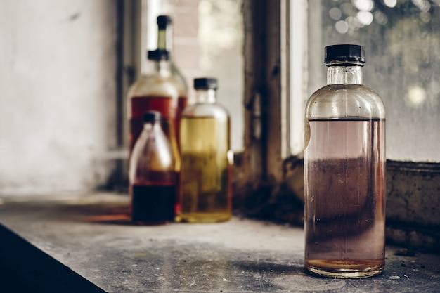 Il colpo del primo piano delle bottiglie di vetro ha riempito di liquidi trasparenti sconosciuti