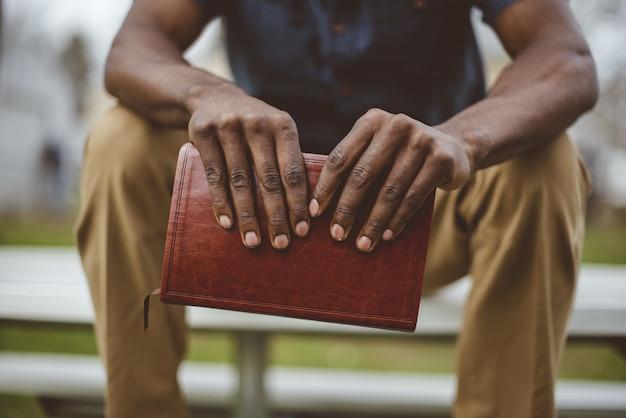 Il colpo del primo piano di un maschio che si siede nel parco mentre tiene la bibbia