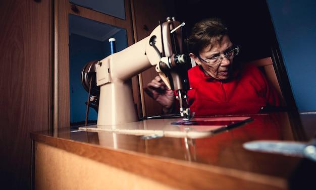 Il colpo dell'interno di bella donna anziana adatta il calzino di cucito facendo uso della macchina di cucitura a sua casa