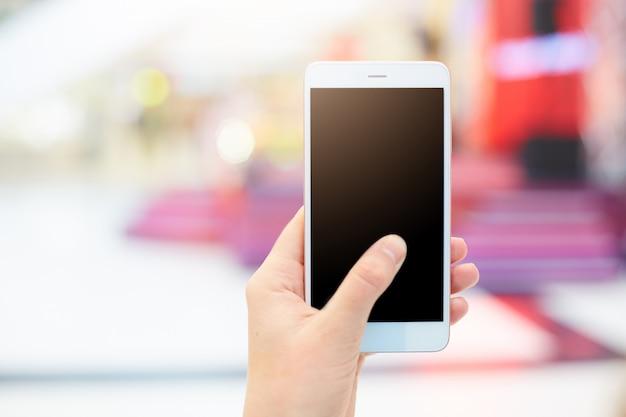 Il colpo della mano femminile tiene lo smart phone con lo schermo in bianco della copia per il vostro contenuto pubblicitario o testo promozionale