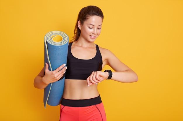 Il colpo di horozontal della donna di forma fisica dopo la sessione di allenamento controlla i risultati su smartwatch nell'app di forma fisica, femmina con il corpo perfetto isolato sopra fondo giallo. stile di vita sano e concetto di sport.