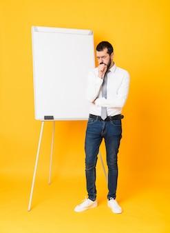 Il colpo integrale dell'uomo d'affari che dà una presentazione sul bordo bianco sopra fondo giallo isolato sta soffrendo di tosse e sta sentendosi male