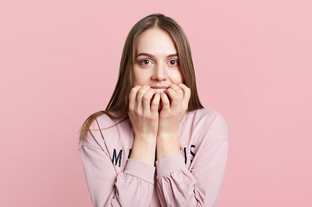 Il colpo isolato del modello femminile grazioso morde le unghie come si sente molto nervoso e imbarazzante